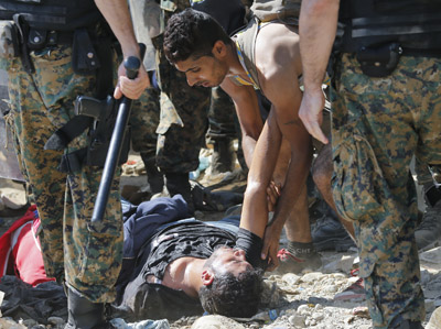 A man helps up an exhausted fellow refugee as they cross the border between Macedonia and Greece, near the town of Gevgelija, Macedonia. (CNS photo/Valdrin Xhemaj, EPA)