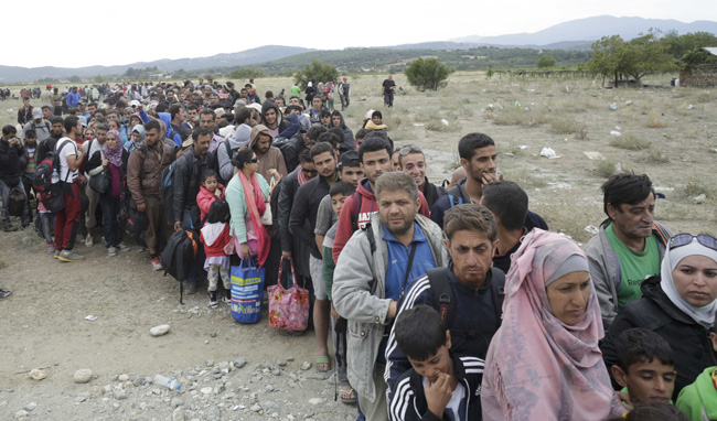 Hundreds of migrants line up to catch a train near Gevgelija, Macedonia, Sept. 7. (CNS photo/Stoyan Nenov, Reuters)