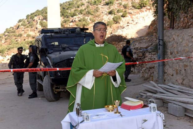 Father Aktham Hijazin of Beit Jalla, West Bank, celebrates Mass Sept. 3 in front of Israeli border police. Israel is uprooting the trees to make the way for the controversial separation barrier in the Cremisan Valley. (CNS photo/Debbie Hill)