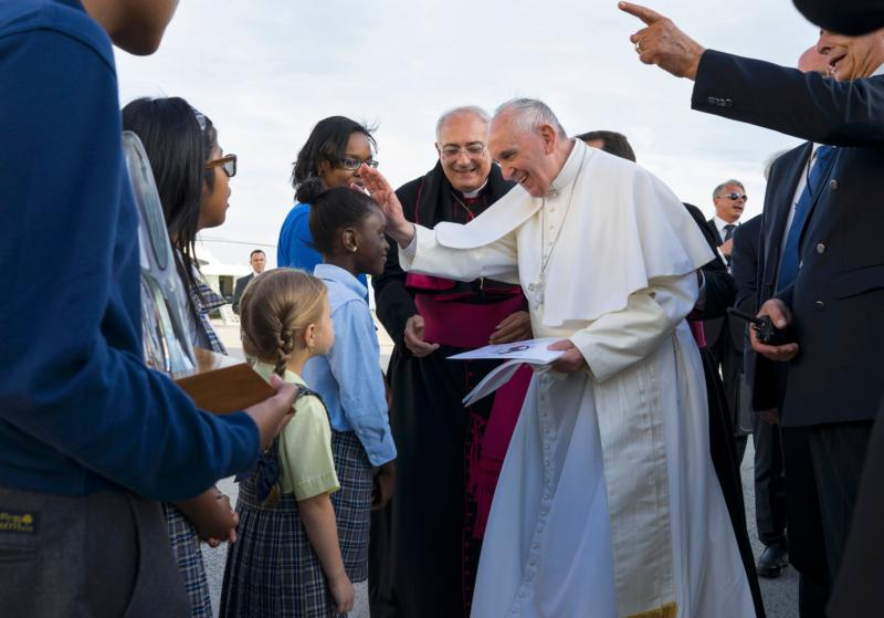 Pope Francis reaches out to Catholic school student Omodelei Ojo of the Brooklyn borough of New York as he is greeted by children upon arrival at John F. Kennedy International Airport Sept. 24 in New York. (CNS photo/Craig Ruttle, pool)