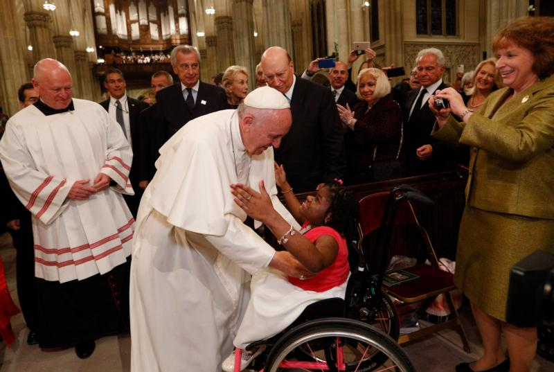 Pope Francis embraces a woman in a wheelchair as he arrives to celebrate vespers in St. Patrick's Cathedral in New York Sept. 24. (CNS photo/Paul Haring) See POPE-NY-VESPERS Sept. 24, 2015.