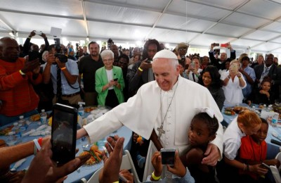 A girl hugs Pope Francis as he visits with people at St. Maria's Meals Program of Catholic Charities in Washington Sept. 24. (CNS photo/Paul Haring)