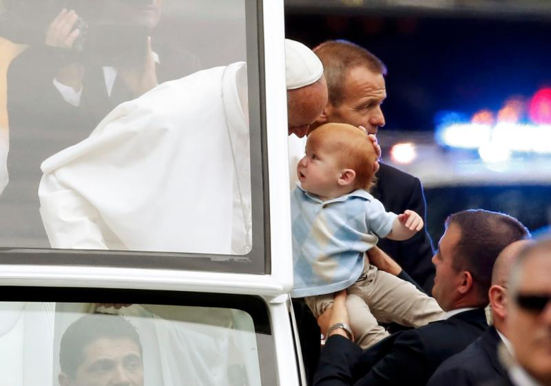 Pope Francis blesses a baby from the popemobile in Philadelphia Sept. 27. (CNS photo/Alex Brandon, pool)