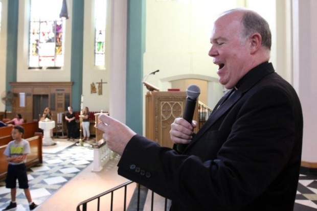 Father Michael P. Kerrigan, parish pastor, announces a winner in a raffle for papal tickets following a Mass at St. John-Visitation Church in the Bronx borough of New York Sept. 13. The parish held a special drawing to select parishioners who will receive tickets to Pope Francis' Mass at Madison Square Garden in New York City Sept. 25. (CNS photo/Gregory A. Shemitz)