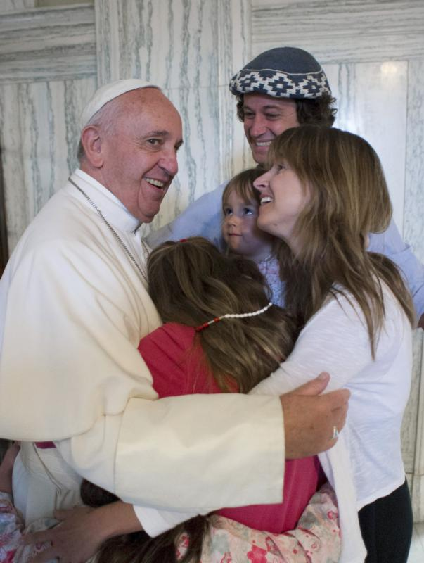 Pope Francis embraces the Walker family of Buenos Aires, Argentina, Sept. 27 in Philadelphia. Catire, Noel and their four children -- Cala, 12, Dimas, 8, Mia, 5, and Carmin, 3 -- traveled 13,000 miles to be with Pope Francis during the World Meeting of Families. (CNS photo/L'Osservatore Romano via Reuters)