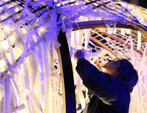"A volunteer ties inside the ""Knotted Grotto"" ribbons containing written intentions for which people have prayed on Friday night, Sept. 25. (Photo by Bob Kelly)"