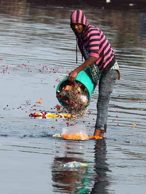 A resident dumps garbage into a river  in New Delhi in 2014.  (CNS photo/Money Sharma, EPA)