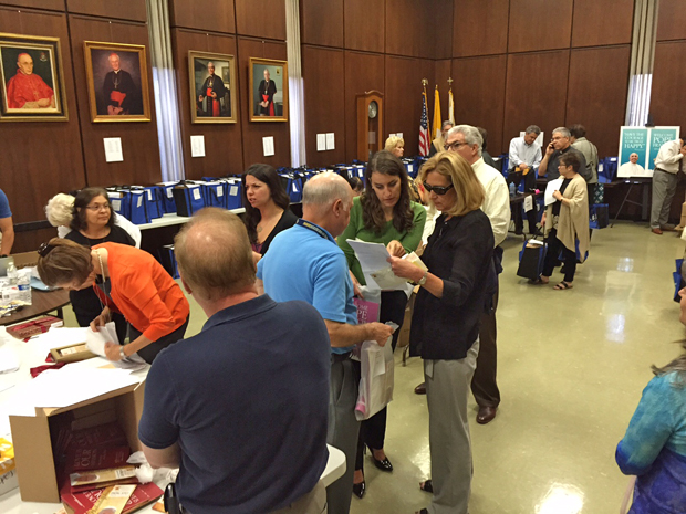 Volunteers organize packages of papal-event materials for distribution to parish representatives.