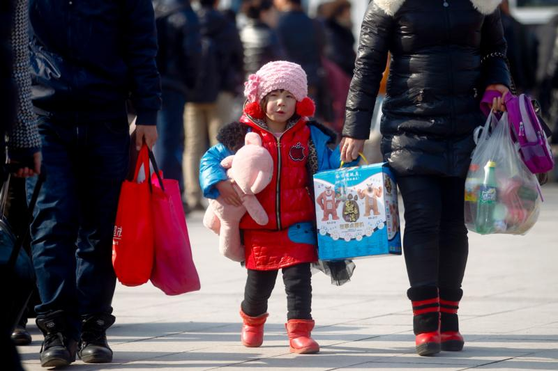 A young girl carrying a stuffed toy holds on to her mother's hand in 2013 as they walk outside the train station in Beijing. China's Communist Party leaders announced they would change the nation's one-child policy, which most strictly applied to Han Chinese living in urban areas of the country. (CNS photo/Diego Azubel, EPA)