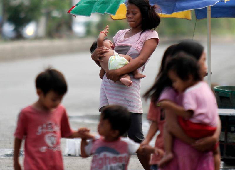 A mother walks with her children in a slum area in Cebu, Philippines, Aug. 30. Catholics from around the world will gather in Cebu in January for the International Eucharistic Congress, an opportunity to remind Catholics that reaching out to all with the Gospel is a key act of mercy. (CNS photo/Jay Rommel Labra, EPA)
