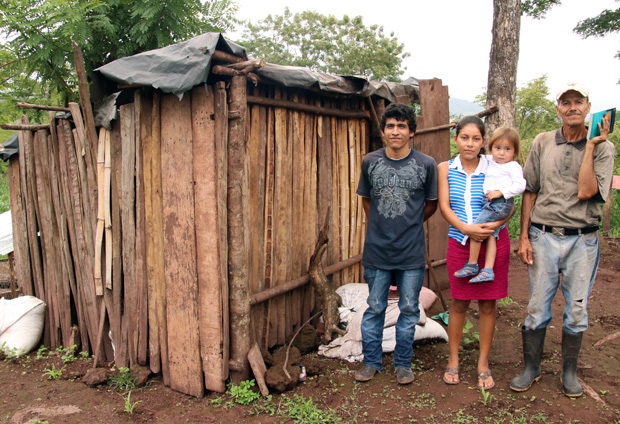 A family stands beside their home, which is typical in the highlands of Nicaragua. Father Chuck's Challenge provides sturdier concrete block structures and other items farming families may need.