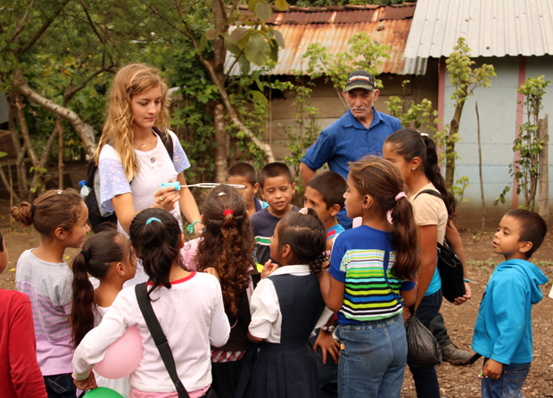 Anneliese Sawick, a young parishioner from the Archdiocese of Philadelphia, shows Nicaraguan children how to have fun with soap bubbles during a recent trip of a dozen Philadelphians visiting residents of villages established by Father Chuck's Challenge.