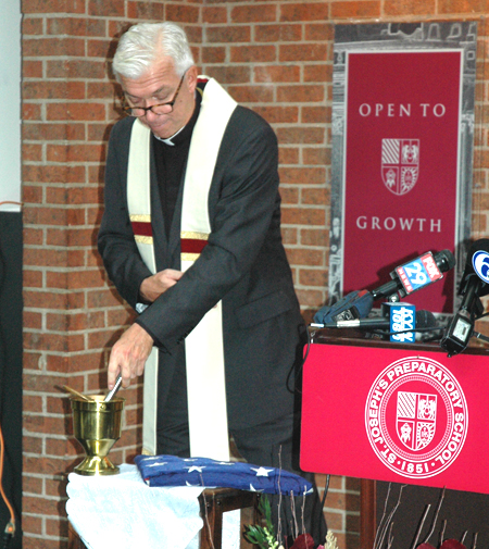 Father John Swope, S.J., blesses the folded American flag with holy water during the rite Oct. 26 at St. Joseph's Preparatory School, Philadelphia.