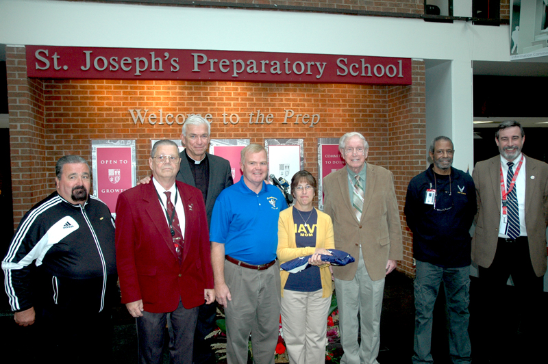 Veterans among the Prep faculty and staff join Jesuit Father John Swope to present the flag to the Taylor family (from left): Jack ONeill (JV soccer coach); Bob Furth (security); Father Swope (president); Paul and Kathy Taylor; Joe Griffin (English); Earl Davenport (facilities) and Dave Fortin (history).