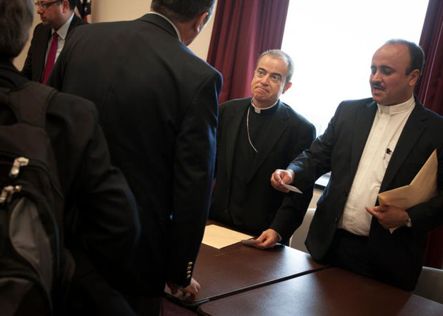 Archbishop Roberto Gonzalez Nieves of San Juan, Puerto Rico, center, listens to a participant after holding a news conference in Washington Sept. 30. The archbishop seeks help from Congress and the White House to ease the island nation's $72 billion debt crisis. (CNS photo/Tyler Orsburn)