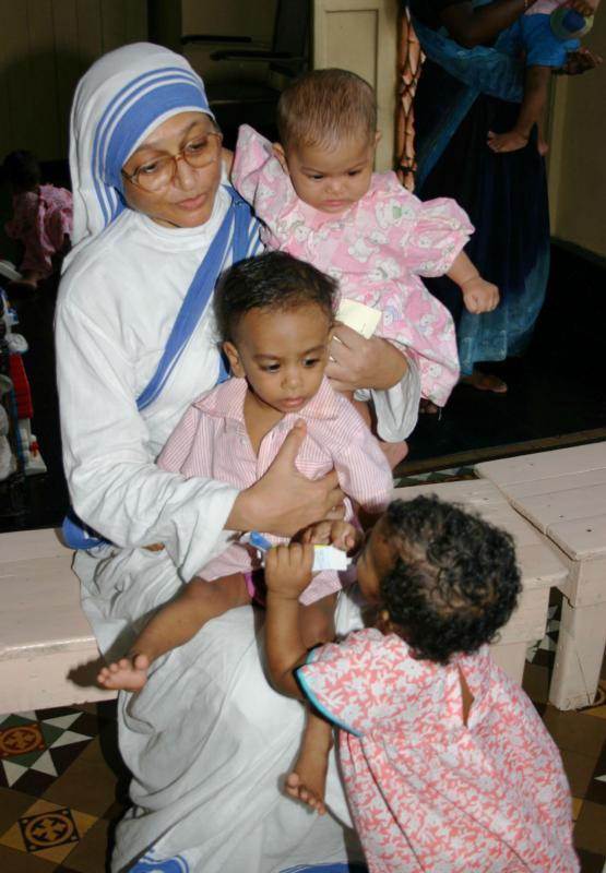 A member of the Missionaries of Charity holds orphan children in 2007 at a center in Kolkata, India. The Missionaries of Charity will close their adoption centers in India, citing new regulations that would allow nontraditional families to adopt children, reported ucanews.com. (CNS photo/Anto Akkara)