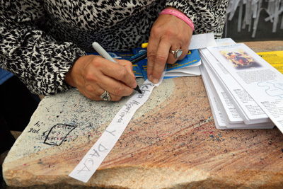 A woman writes her prayer intention on a ribbon to be tied on the Knotted Grotto. (Bob Kelly)
