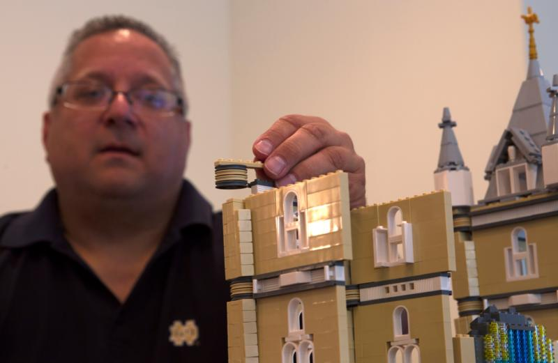 Father Bob Simon, pastor of St. Catherine of Siena Parish in Moscow, Pa., places a Lego piece on a model church he is building in a spare room in his rectory Oct. 24. Father Simon says his Lego-building hobby has served as an evangelization tool. (CNS photo/Chaz Muth)