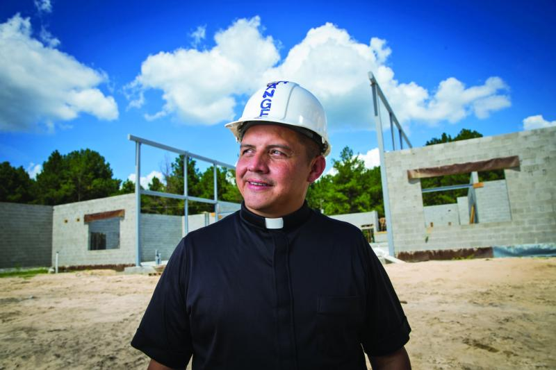 Father Fredy Angel of Ray City, Ga., poses for a photo at St. Anthony of Padua Church's construction site Aug. 15. The Georgia priest won this year's Catholic Extension Lumen Christi Award. (CNS photo/Rich Kalonick, Catholic Extension)