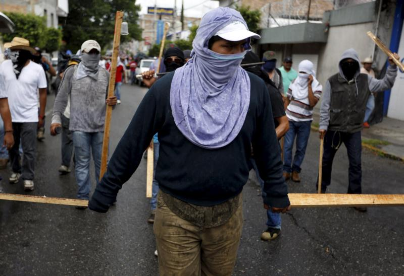 Demonstrators hold batons as they take part in a Sept. 27 march to mark the first anniversary of the disappearance of 43 students from a teachers college in the southern Mexican state of Guerrero. The Mexican bishops' conference and the Vatican have confirmed Pope Francis will visit Mexico in 2016. (CNS photo/Jorge Dan Lopez, Reuters)