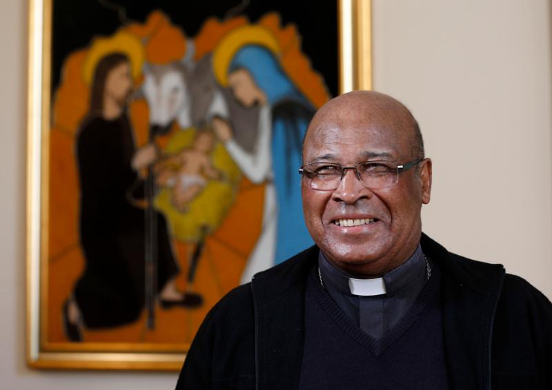 Cardinal Wilfrid Napier of Durban, South Africa, is pictured near an image of the Holy Family after an interview with Catholic News Service in Rome Oct. 7.  (CNS photo/Paul Haring)