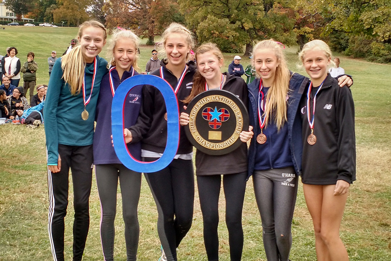 The girls' cross-country squad of Cardinal O'Hara High School show pride in their Catholic League championship victory.