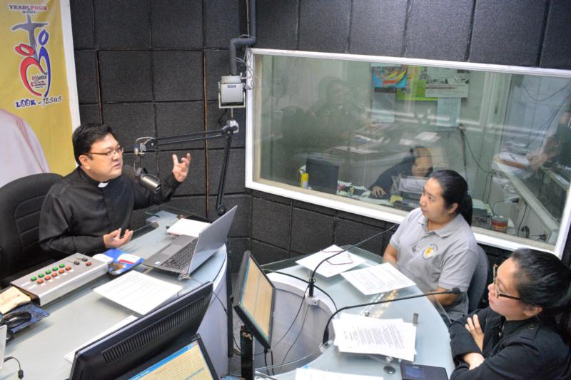 "Dominican Father Winston Cabading interviews Jing de los Reyes, administrator of the Archdiocese of Manila Office of Exorcism, during the radio program ""Light in the Darkness"" Oct. 24 at Radio Veritas in Quezon City, Philippines. (CNS photo/Simone Orendain)"