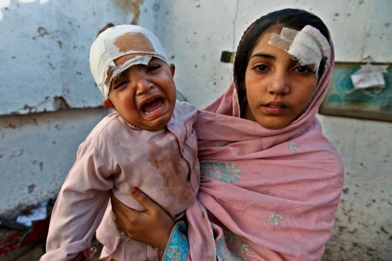 A Pakistani woman holds an injured child in their home Oct. 26 following a magnitude-7.5 earthquake in Peshawar, Pakistan. As the death toll from the earthquake in Pakistan and Afghanistan continued to rise, Pope Francis called for prayers and concrete aid for survivors. (CNS photo/Bilawal Arbab, EPA)