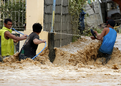 Residents hold on to a plastic hose and an electrical wire Oct. 19 while trying to cross a flooded road amid a strong current after Typhoon Koppu hit the Philippine province of Nueva Ecija. (CNS photo/Erik De Castro, Reuters)