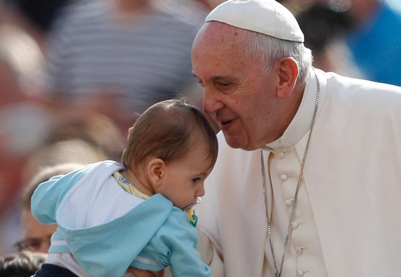 Pope Francis greets a baby during his general audience in St. Peter's Square at the Vatican Oct. 7. The pope said that when families mirror God's love for all, they teach the church how it should relate to all people. (CNS photo/Paul Haring)