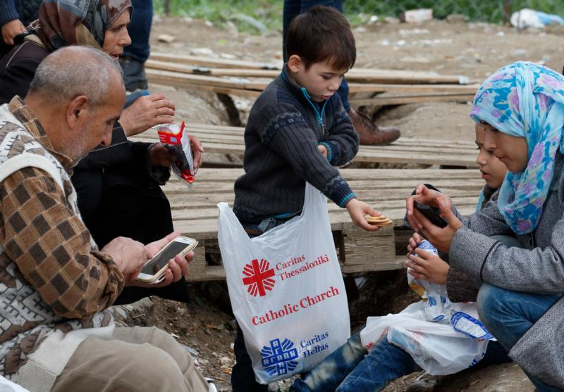 A boy hands cookies from a food bag given by Caritas to family members at a transit camp for refugees in Idomeni, Greece, on the border of Macedonia Oct. 19. Thousands of refugees are arriving into Greece from Syria, Afghanistan, Iraq and other countries and then traveling further into Europe. (CNS photo/Paul Haring) See TAGLE-REFUGEES-IDOMENI Oct. 19, 2015.