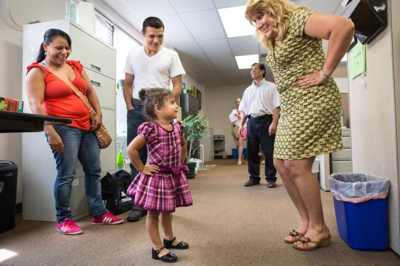 A family who immigrated from El Salvador meets with immigration caseworker Silvia Martinez, right, earlier this year at the Catholic Charities office in St. Louis. (CNS photo/Lisa Johnston, St. Louis Review)