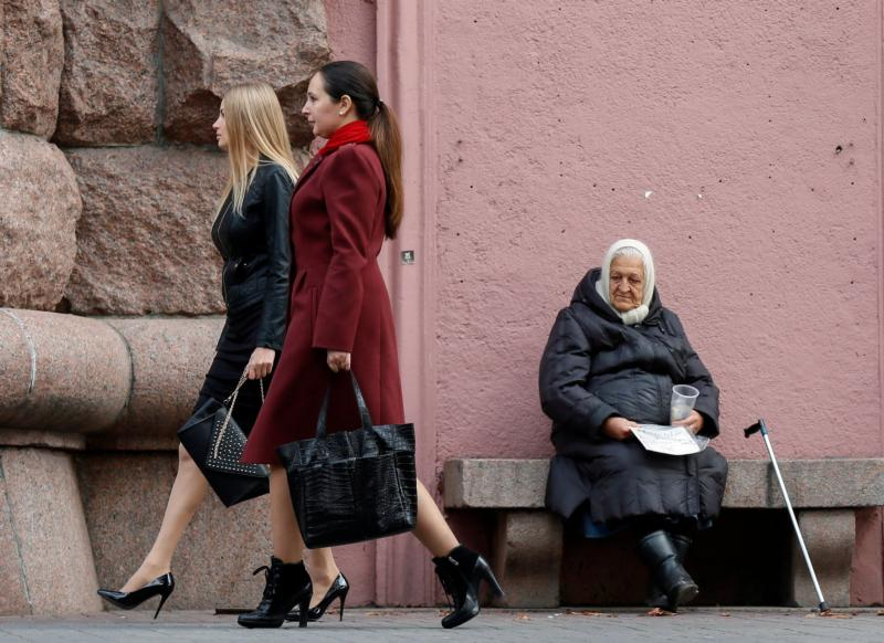 An elderly woman asks for money as women pass her by in Kiev, Ukraine, Oct.23. While they did not grab headlines, the topics of elderly and people with disabilities, openness to life and the plight of migrants and refugees were also on the agenda of the Synod of Bishops on the family. (CNS photo/Sergey Dolzhenko, EPA)