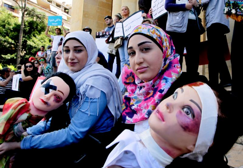 Protesters carry mannequins showing signs of domestic violence in Beirut May 30. Some synod observers said women should not to return to abusive husbands. (CNS photo/Nabil Mounzer, EPA)