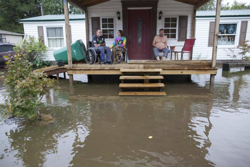 People sit on their porch as floodwaters surround their home in Myrtle Beach, S.C., Oct. 5. (CNS photo/Randall Hill, Reuters)