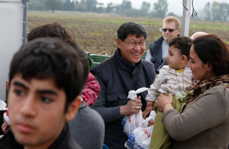 Cardinal Luis Antonio Tagle of Manila gives a food bag to a refugee family as they arrive at a transit camp in Idomeni, Greece, on the border of Macedonia Oct. 19. Thousands of refugees are arriving into Greece from Syria, Afghanistan, Iraq and other countries and then traveling further into Europe. (CNS photo/Paul Haring)