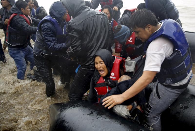 Afghan mother holds her baby as she struggles to disembark raft during a rainstorm in Lesbos, Greece, Oct. 23. Members of Congress were told in Washington that Europe's refugee crisis demands global response. (CNS photo/Yannis Behrakis, Reuters)