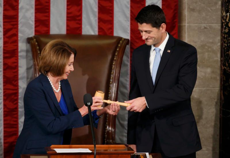 Former U.S. House Speaker and current Minority Leader Nancy Pelosi, D-Calif., hands incoming House Speaker Paul Ryan, R-Wis., the gavel after his election on Capitol Hill in Washington Oct. 29. In his acceptance speech Ryan pledged to get the chamber working for the American people again. (CNS photo/Gary Cameron, Reuters)