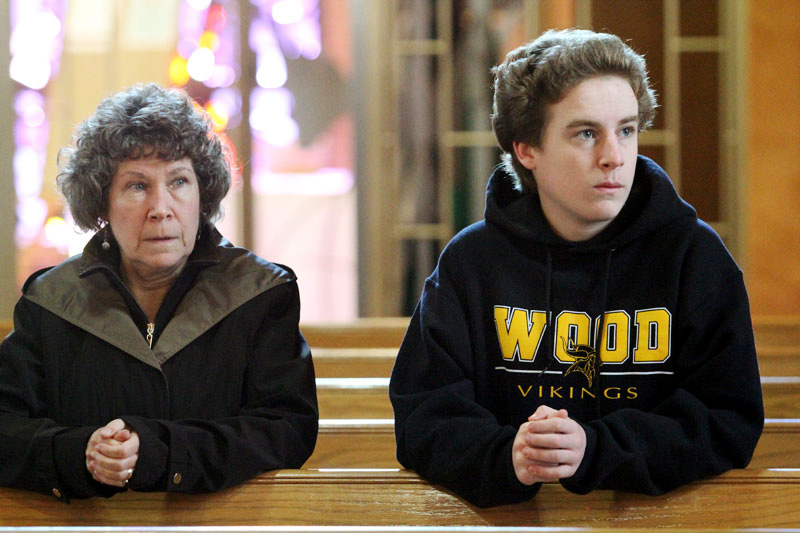 Marie Graham and her son Brian pray together before Mass.