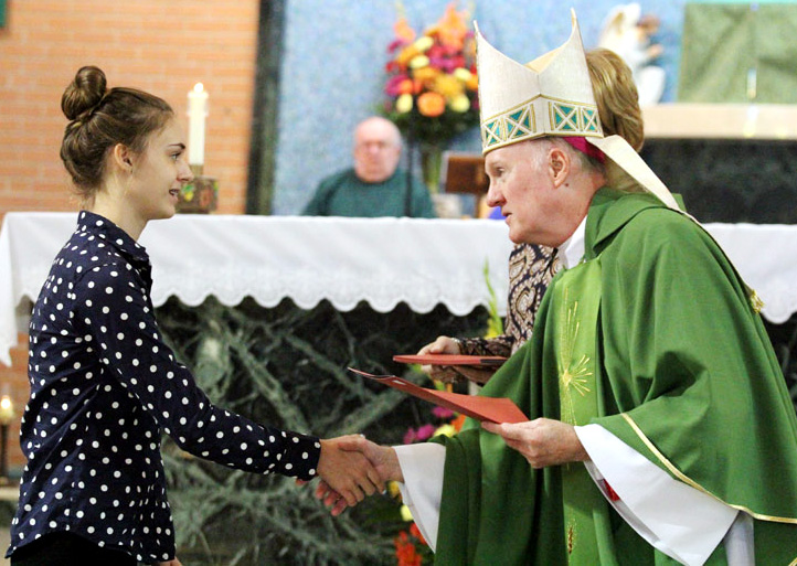Julianna Kissinger from St Francis of Assisi School in Sprinfield receives her Missionary Childhood Association 2014-15 Christmas Coloring Contest Award from Bishop Michael Fitzgerald.