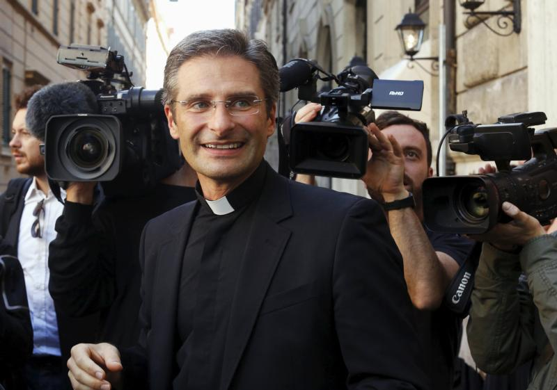 Msgr. Krzysztof Charamsa smiles as he leaves a news conference he called Oct. 3 to announce he is gay and has a partner. The Vatican spokesman said, given Msgr. Charamsa's public announcement, it would be impossible for the monsignor to continue working at the Vatican or teaching at pontifical universities.(CNS photo/Alessandro Bianchi, Reuters)