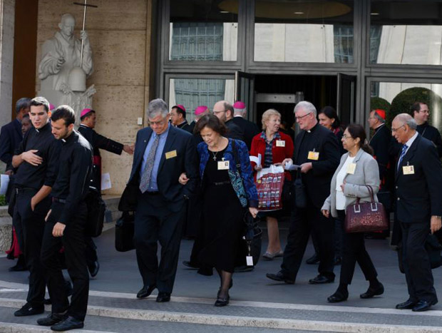 Anthony and Catherine Wally Witczak (at center in blue), from Philadelphia, and other delegates leave a session of the Synod of Bishops on the family at the Vatican Oct. 15. The couple are observers at the synod. (CNS photo/Paul Haring)