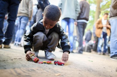 Refugee boy plays with a toy car while refugees wait for registration in Berlin,ÊGermany, Oct. 1. (CNS photo/Kay Nietfeld, EPA)