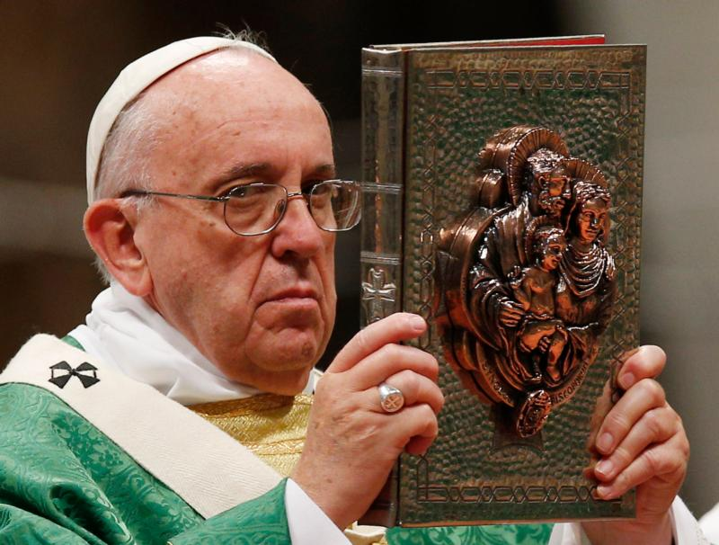 Pope Francis raises the Book of the Gospels during the opening Mass of the Synod of Bishops on the family in St. Peter's Basilica at the Vatican Oct. 4. The cover of the book is decorated with an image of the Holy Family. (CNS/Paul Haring)