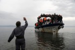 A resident waves to an overcrowded fishing boat carrying migrants after they arrived on the Greek island of Lesbos Oct. 11 after crossing the Aegean sea from Turkey. (CNS photo/Yannis Kolesidis, EPA)
