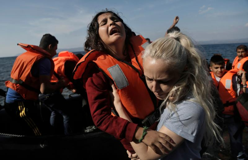 A Syrian girl reacts as she helped by a volunteer upon her Oct. 9 arrival from Turkey to the Greek island of Lesbos.  (CNS photo/Yannis Kolesidis, EPA)