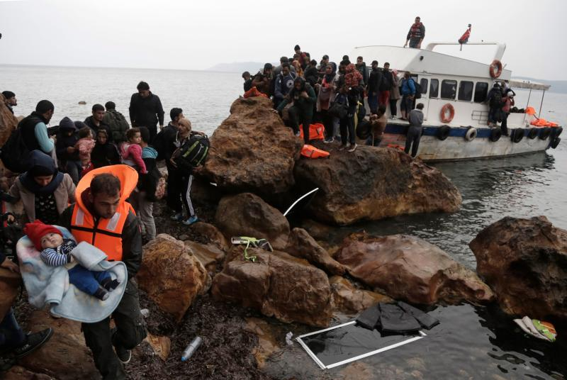 Migrants from Syria arrive on the Greek island of Lesbos Oct. 11 on an overcrowded fishing boat after crossing the Aegean sea from Turkey.  (CNS photo/Yannis Kolesidis, EPA)