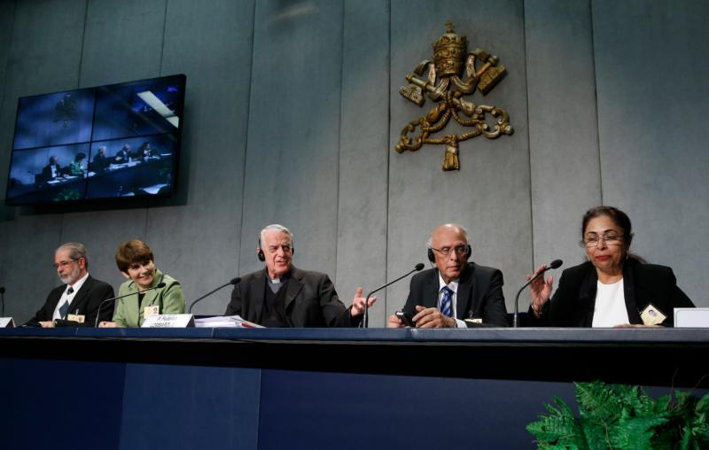 Jesuit Father Federico Lombardi, papal spokesman, introduces two couples attending the Syond of Bishops on the family during a media briefing on the synod at the Vatican Oct. 12. At left are Ketty and Pedro De Rezende from Brazil; at right are Ishwar and Penny Bajaj from India. (CNS/Paul Haring)