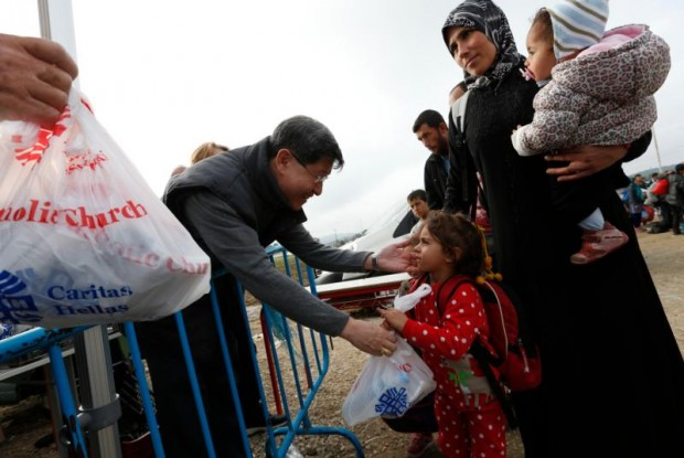 Cardinal Luis Antonio Tagle of Manila gives a food bag to a refugee family as they arrive at a transit camp in Idomeni, Greece, on the border of Macedonia Oct. 19. (CNS photo/Paul Haring)