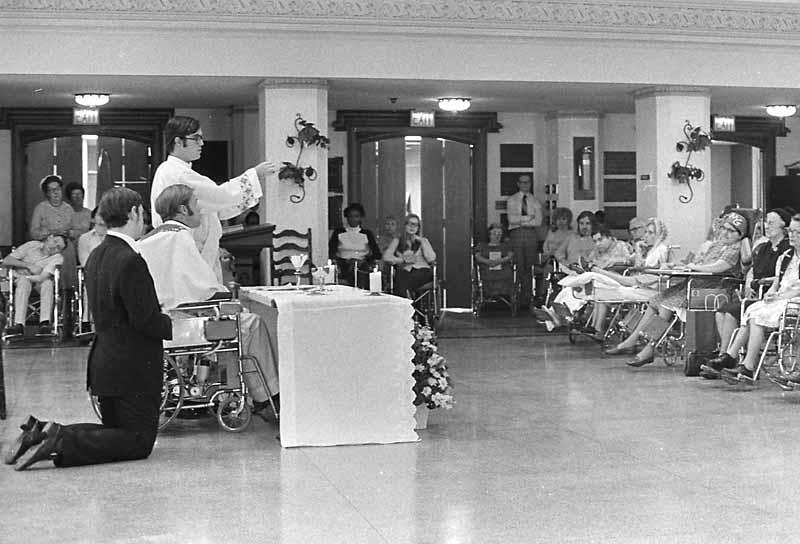 Father Atkinson celebrates his first Mass, with the help of another priest, at the Fieldhouse at Villanova University, in this 1974 file photo. Philadelphia Archdiocesan Historical Research Center: Robert and Theresa Halvey Photograph Collection)